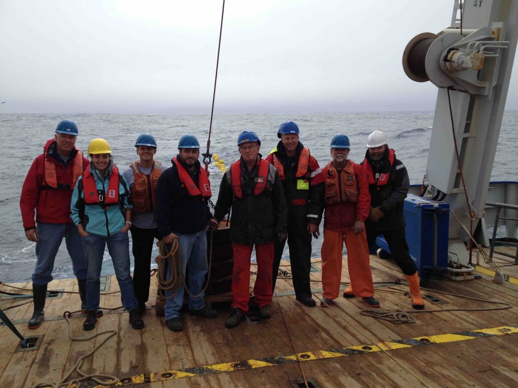 The mooring team with R/V Pelagia deck crew, standing by a mooring anchor while towing the mooring to its final deployment spot.