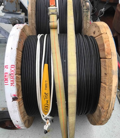 Photo of a wooden spool on the back deck of the ship, with a portion of the mooring cable wrapped around it.